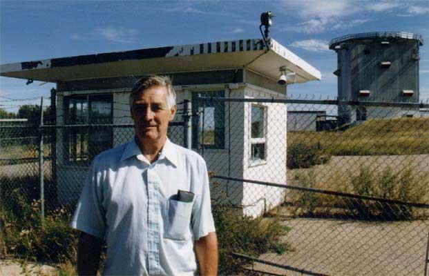 Retired radar technician John Armstrong stands before an old guardhouse at a NORAD radar site, 1997, CFS Dana, Saskatchewan.